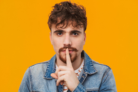 Close up of a pensive young bearded man casually dressed standing isolated over orange, showing silence gesture