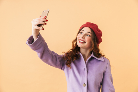 Portrait of beautiful girl 20s in coat and hat taking selfie photo on mobile phone while standing isolated over beige background