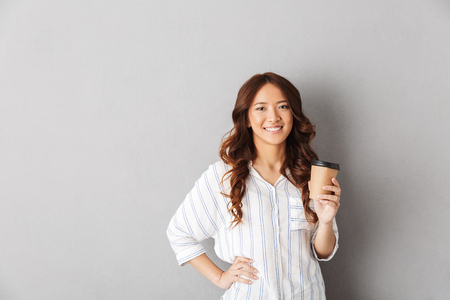 Cheerful asian woman standing isolated over gray background, drinking coffee