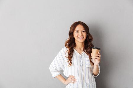 Vrolijke Aziatische vrouw staande geïsoleerd over grijze achtergrond, koffie drinken