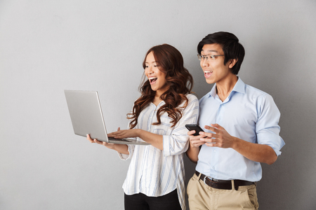 Happy asian couple standing isolated over gray background, using laptop computer, holding mobile phone