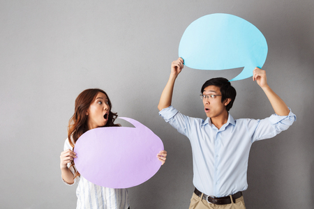 Confused asian couple standing isolated over gray background, holding empty speech bubble, having an argument