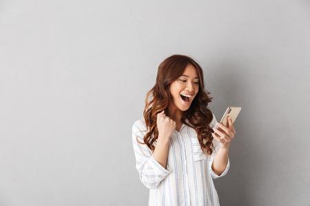 Vrolijke Aziatische vrouw staande geïsoleerd over grijze achtergrond, mobiele telefoon vasthouden, vieren