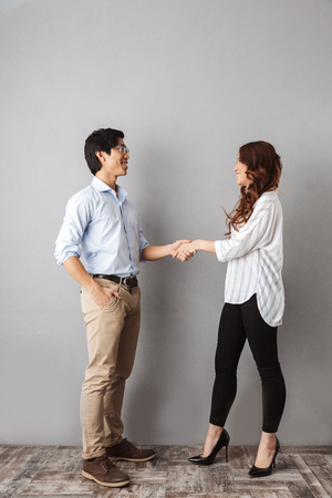 Full length of cheerful asian couple standing over gray background, shaking hands