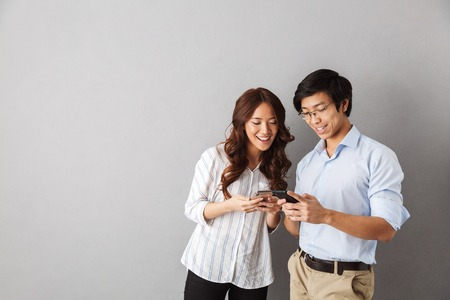 Happy asian couple standing isolated over gray background, using mobile phones 스톡 콘텐츠