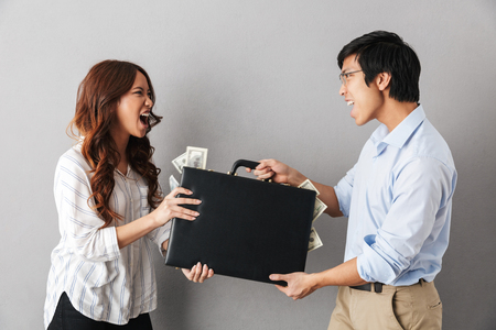 Angry asian couple standing isolated over gray background, fighting for a briefcase full of money banknotes