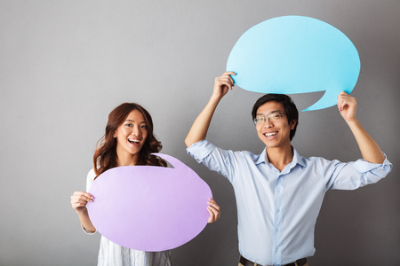 Cheerful asian couple standing isolated over gray background, holding empty speech bubble