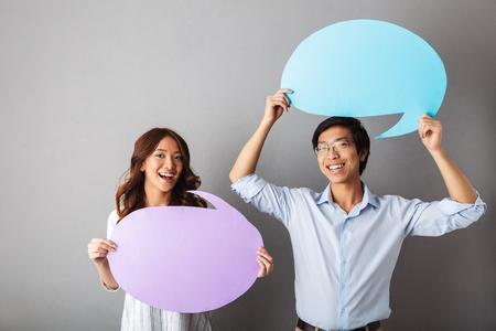Joyeux couple asiatique debout isolé sur fond gris, tenant une bulle de dialogue vide Banque d'images