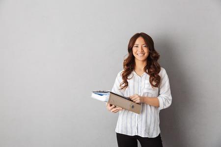 Sonriente mujer de negocios asiática de pie sobre fondo gris