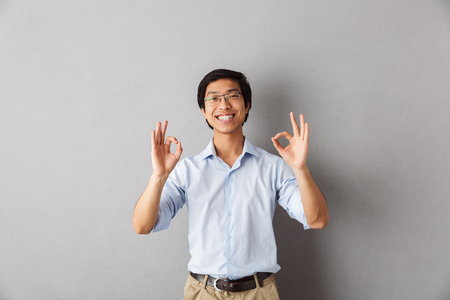 Happy asian man standing isolated over gray background, showing ok