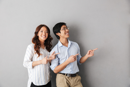 Cheerful asian business couple standing isolated over gray background, pointing fingers away at copy space