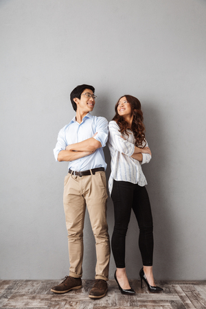 Full length of cheerful asian couple standing back to back over gray background 版權商用圖片
