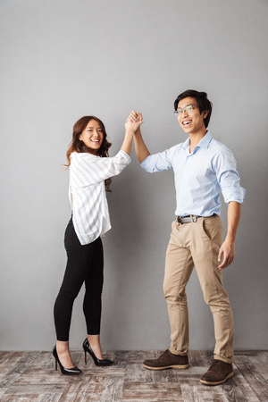 Full length of cheerful asian couple standing over gray background, giving high five