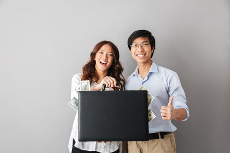 Happy asian couple standing isolated over gray background, holding briefcase full of money banknotes Imagens