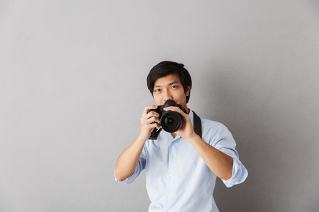 Happy asian man standing isolated over gray background, taking a picture with photo camera
