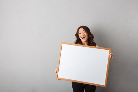Cheerful asian woman standing isolated over gray background, showing blank board