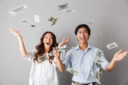 Gelukkig Aziatisch zakenpaar dat zich onder de douche van geldbankbiljetten bevindt die over grijze achtergrond wordt geïsoleerd Stockfoto