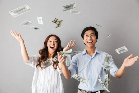 Happy asian business couple standing under money banknotes shower isolated over gray background