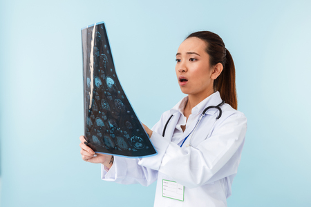 Photo of a young shocked woman doctor posing isolated over blue wall background with x-ray.