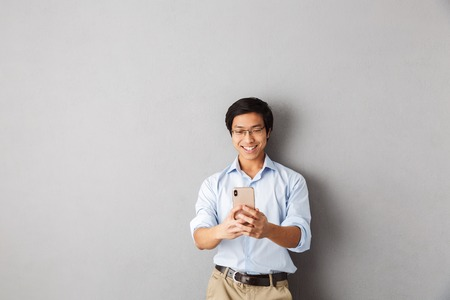 Smiling asian business man standing isolated over gray background, using mobile phone
