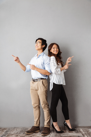 Full length of cheerful asian couple standing over gray background, pointing fingers at copy space