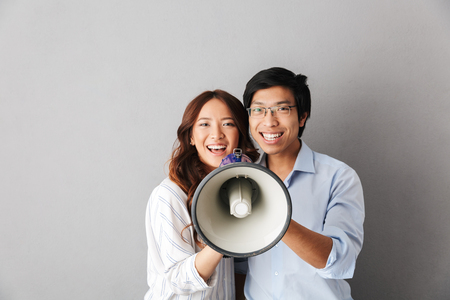 Happy asian business couple standing isolated over gray background, holding loudspeaker
