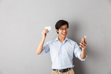 Smiling asian business man standing isolated over gray background, holding mobile phone, showing plastic credit card Stock Photo