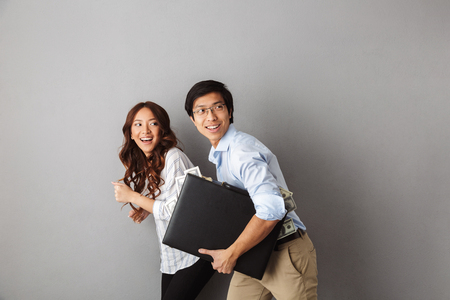 Happy asian couple running away isolated over gray background, holding briefcase full of money banknotes