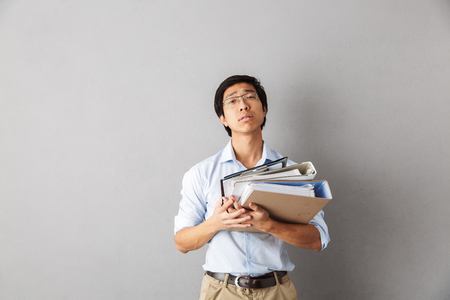 Tired asian man standing isolated over gray background, carrying folders with documents