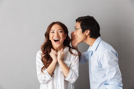 Excited asian couple standing isolated over gray background, telling secrets to each other