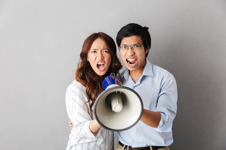 Angry asian business couple standing isolated over gray background, holding loudspeaker