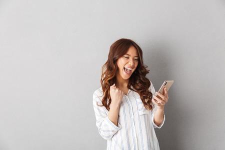 Alegre mujer asiática que se encuentran aisladas sobre fondo gris, sosteniendo el teléfono móvil, celebrando