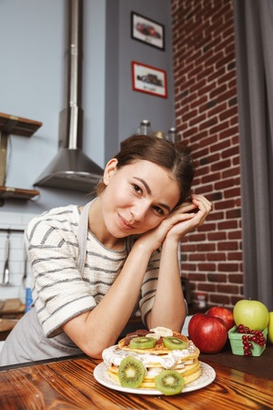 Happy young woman at the kitchen at home, showing prepared pancakes with fruits and cream on a table