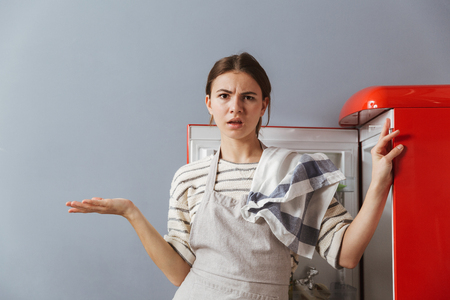 Confused young woman standing at the fridge in kitchen at home