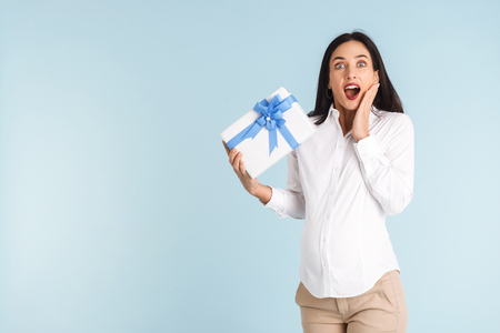 Image of a beautiful shocked young pregnant business woman isolated over blue wall background holding gift box.