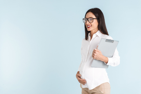 Image of a young pregnant business woman isolated over blue wall background holding clipboard.