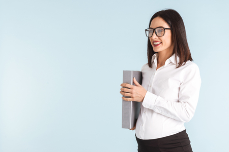 Photo of a young pregnant business woman isolated over blue wall background holding folder.