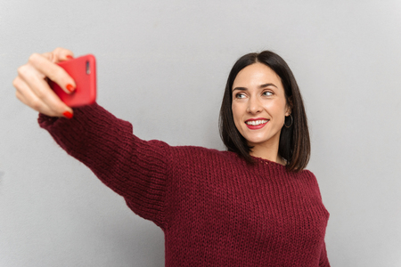 Picture of pretty young woman dressed in burgundy sweater take selfie by mobile phone isolated over grey wall background. Banque d'images