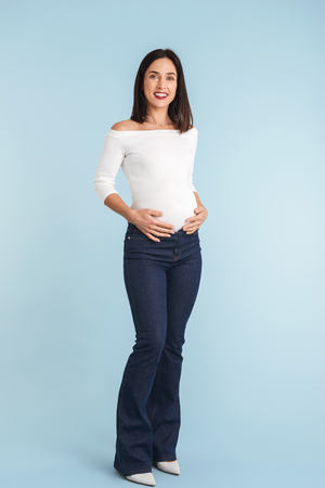 Photo of a young pregnant woman isolated over blue wall background.