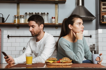 Unhappy young couple sitting at the kitchen during lunch at home, having a problem, holding mobile phone