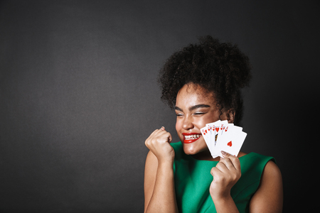 Excited african woman wearing dress showing playing cards isolated over black background, celebrating success