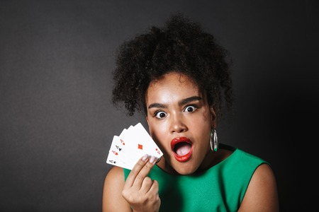 Excited african woman wearing dress showing playing cards isolated over black background