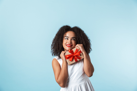 Cheerful young african woman wearing dress celebrating isolated, holding present box