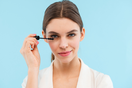 Photo of beautiful young woman posing isolated over blue background holding lash mascara doing makeup.