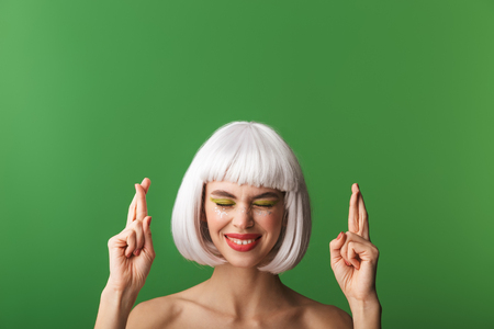 Attractive worried young topless woman wearing short white hair standing isolated over green background, holding fingers crossed for good luck