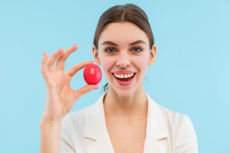 Photo of beautiful young woman posing isolated over blue background holding lip balm.