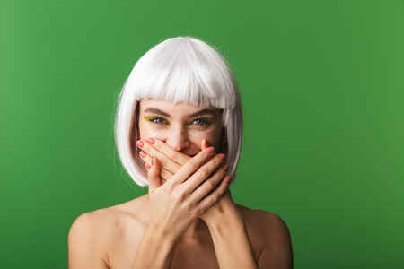 Attractive young topless woman wearing short white hair standing isolated over green background, covers face with hands Stock fotó