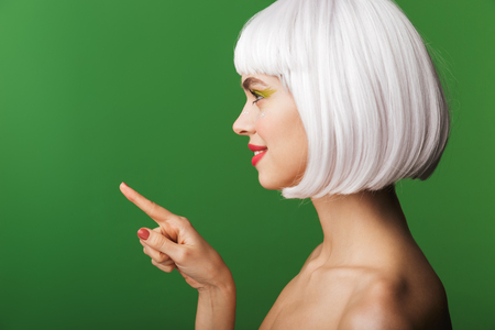 Attractive young topless woman wearing short white hair standing isolated over green background, pointing finger at copy space