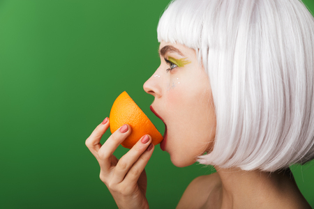 Attractive young topless woman wearing short white hair standing isolated over green background, eating sliced orange