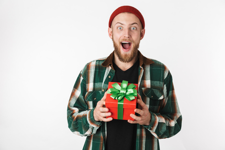 Portrait of handsome bearded guy wearing hat and plaid shirt holding present box while standing isolated over white background Stock Photo